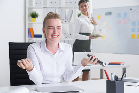 dapper: Desperate blond business lady sitting at her workplace. Her colleague in background is smiling pleased with her failure. Concept of competition at work