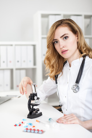 expertize: Woman doctor with microscope sitting in lab in white lab coat. Concept of forensic work and criminology