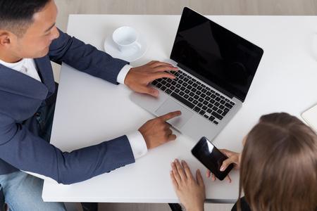 アジア系のビジネスマンは、彼の同僚は、彼女の携帯電話をチェック中に彼のラップトップで働きます。コンセプト何だろう私たちを行うインター