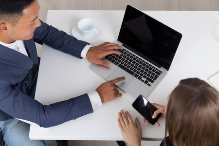 Asian businessman working at his laptop while his colleague is checking her phone. Concept of what would we do without internet? Banque d'images