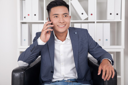 told: Asian businessman is told on phone that his wife just have given birth to their first son. Concept of news from stork Stock Photo
