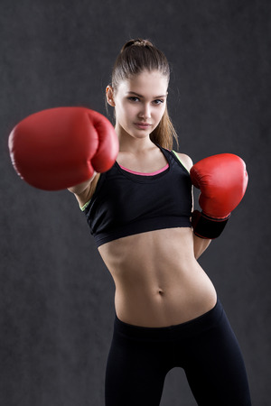 girl punch: Girl boxer in red boxing gloves making powerful punch. Concept of fighting and letting excessive aggression out Stock Photo
