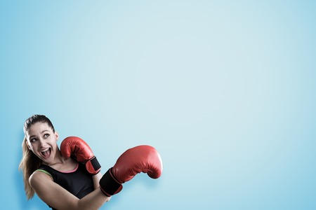 girl punch: Rookie girl boxer about to take a punch standing against blue background. Concept of going in for sports. Stock Photo