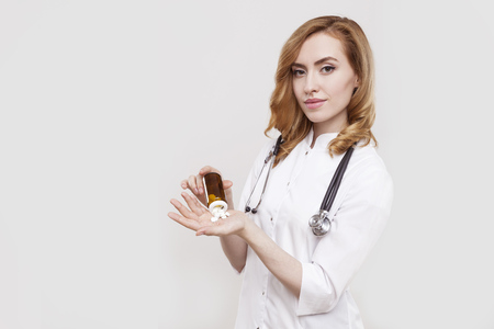 prescribed: Portrait of beautiful woman doctor spilling pills on her palm. Concept of prescribed medication. Mock up