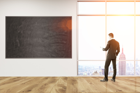 looking at view: Man in suit standing in office corridor with blackboard on wall looking at city view through big window. Concept of management. 3d rendering. Mock up. Toned image.