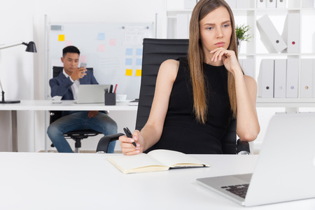 Pensive businesswoman considering all alternatives while her Asian colleague is relaxing and texting to his boyfriend. Concept of good and bad employees