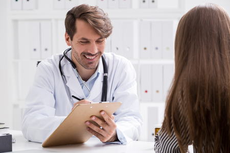 Smiling doctor taking notes. Patient explains her symptoms. Treatment going well. Concept of healthy patient Stock Photo