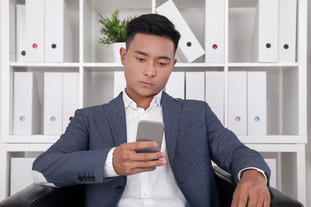socialization: Asian manager looking at his phone screen and texting. Concept of digital world communication and socialization. Stock Photo