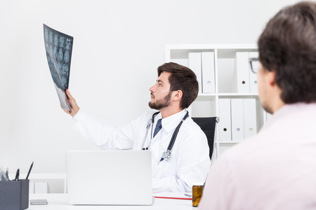 x ray image: Brain surgeon is looking at x ray image of his patient and trying to give him the right diagnosis. Concept of scrupulous doc