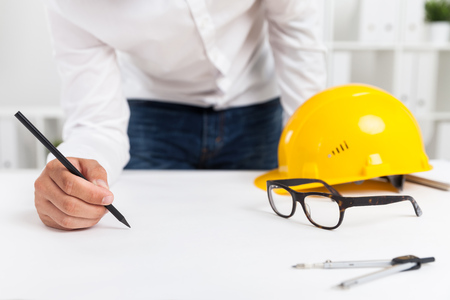 hat project: Engineer working at blueprint in his office with bookshelves and binders. Hard hat, glasses and compass lie on table. Concept of building project Stock Photo