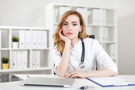 Serious woman doctor sitting in her office with stethoscope around neck near laptop on desk. Bookshelves with binders in background. Concept of good specialist
