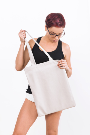 product placement: Girl in white shorts holding big canvas bag and looking down. She is dressed in black tank top and wearing glasses with black frame. Concept of product placement. Mock up. white background.