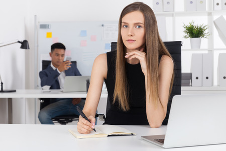 speculative: Pretty business lady in black dress is thinking about her speech at tomorrows board meeting. Her Asian colleague is checking his social media in smartphone