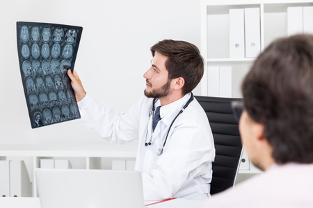 x ray image: Serious doctor is looking at x ray image of his patient who is also staring at them trying to understand. Concept of medical examination Stock Photo