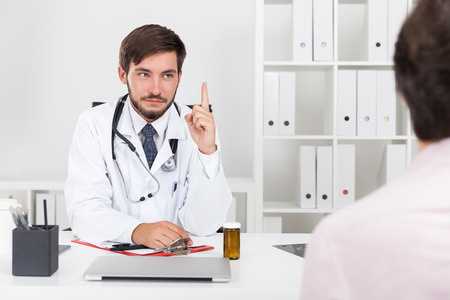 Doctor explaining to his patient harmful effects of compulsive drinking. Concept of sober lifestyle. Stock Photo