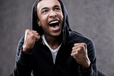 he is a traditional: African American man who has just found out that he had won in traditional national lottery. Concept of good luck Stock Photo