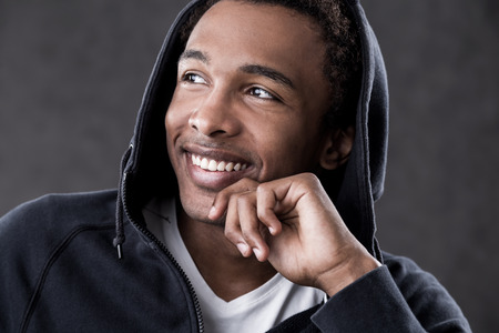 cheerfulness: Smiling African American man looking sideways. Concept of cheerfulness and positive thinking