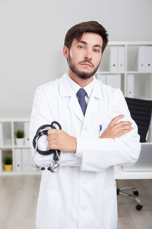 menace: Serious male doctor is holding his stethoscope and standing with arms folded in his office looking at view with menace.