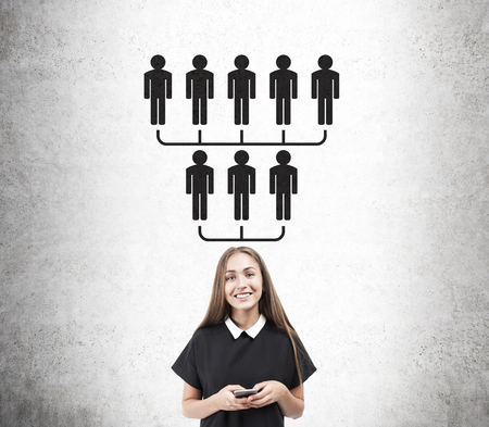 meet up: Smiling blond woman standing near concrete wall with upside down pyramid sketch. Concept of net marketing Stock Photo