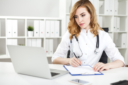 Serious woman doctor is taking notes looking at computer screen in her office. Concept of working with information to give the right diagnosis