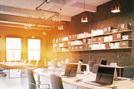 Intérieur de bureau ensoleillé avec de longues tables d'ordinateur, des ordinateurs portables, des lampes et des étagères sur les murs. Concept de studio de design. Rendu 3D, image tonique