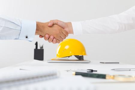 Auftragnehmer und Firmenleiter, die einen Deal abschütteln, der die Hände schüttelt. Konzept der neuen Beschäftigungsmöglichkeiten und Stadtentwicklung