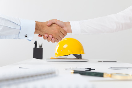 Contractor and company executive sealing a deal shaking hands. Concept of new job opportunities and city development