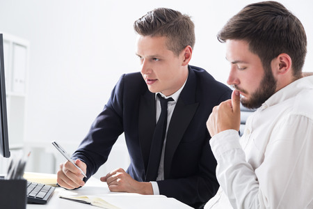 finance manager: Two business partners working together at computer table looking at screen and their notes. Concept of brainstorming.