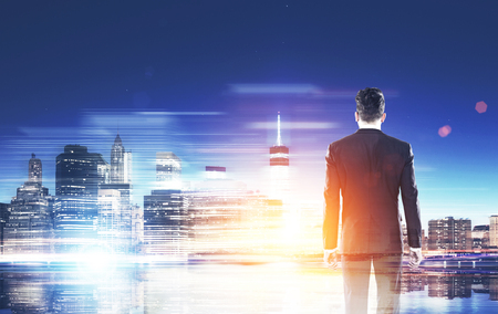 looking at viewer: Man in suit standing with back to viewer and looking at big city panorama. Concept of international trade and business companies. Toned image