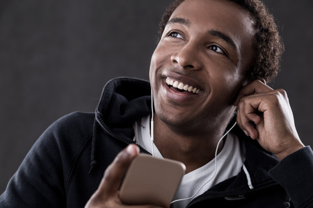 african business man: Cheerful African American man listening to music with headphones and cellphone. Concept of show business and glamour