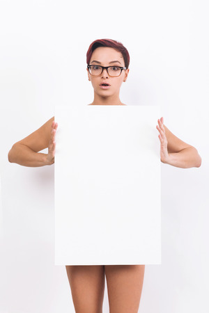Naked woman with short red hair in glasses is standing with large blank placard in her hands covering her torso. Concept of product placement. White background. Banque d'images