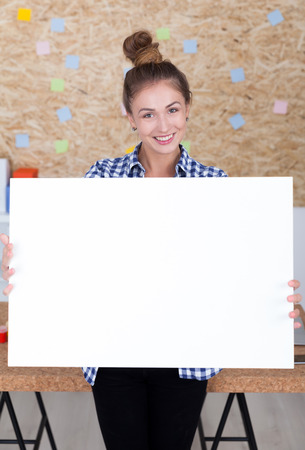 big cork: Hipster girl with bun in blue checkered shirt is holding large horizontal placard. Concept of advertisement. Mock up Stock Photo