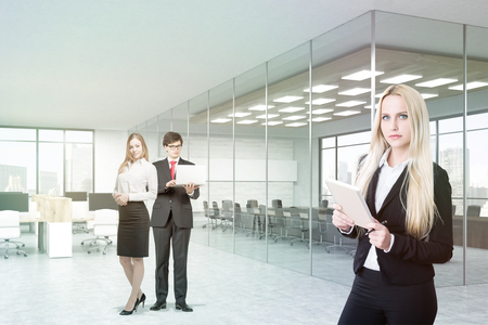 toiling: Businesspeople portrait in office. Man and woman stand in background holding laptop. Blond woman in foreground with notepad. Conference room with concrete walls. 3d rendering. Stock Photo