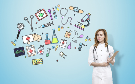 medical field: Doctor in smock standing near blue wall with medicine sketches. Concept of medical field of work
