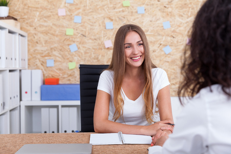met: Business lady talking to firm client in her office with white book shelves and cork board. Concept of business process Stock Photo