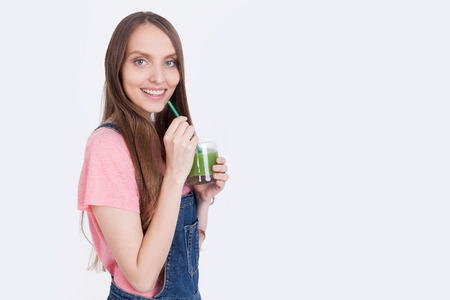 broadly: Side view of girl in pink T-shirt and jeans overalls holding glass with green smoothie with straw and smiling broadly. Concept of healthy eating habits and avoiding junk food. Mock up Stock Photo