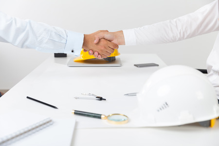 hard hats: Two men in shirts are shaking hands. Hard hats, magnifier and compass lie on table. Concept of construction and renovation. Stock Photo