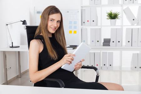mona lisa: Smiling business woman in black dress holding large tablet with both hands and smiling Mona Lisa smile to camera. Concept of your cunny colleague Stock Photo