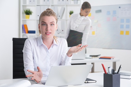 rudeness: Blond business woman is surprised by rudeness of her male colleagues opinion about her working competence. Concept of mans world Stock Photo