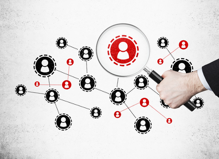Red and black startup sketch on concrete wall. Mans hand holding magnifying glass above one of the icons. Concept of interesting startup idea or recruitment process. Stock Photo