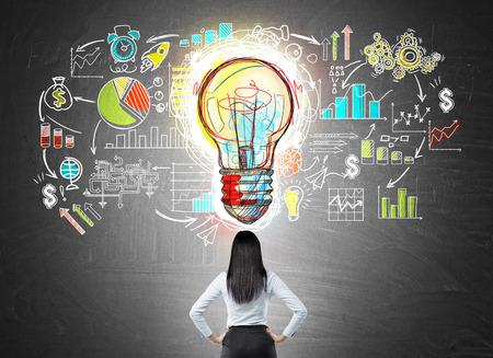 腰の真ん中に大きな電球アイコンで黒板にカラフルなスタートアップのスケッチを見て上の手で実業家の背面します。明るい考えの概念。