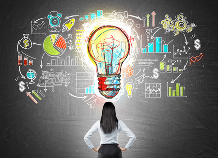 Rear view of businesswoman with hands on waist looking at colorful startup sketch on chalkboard with large light bulb icon in middle. Concept of bright idea.