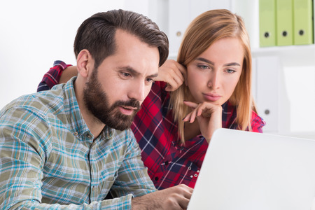 editor: Two engineers working at current project. Man is showing his colleague what he has done. She is impressed and sorry she hasnt figured it out. Concept of teamwork Stock Photo
