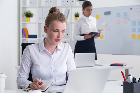 difficult task: Business woman is looking at her laptop screen and making notes. Her colleague is checking her notebook standing near whiteboard. Concept of difficult task Stock Photo