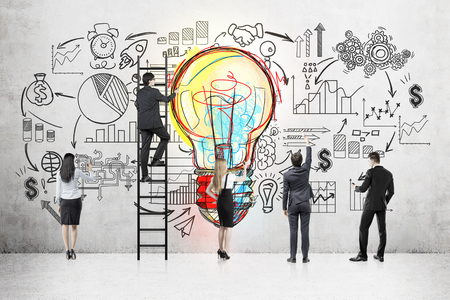 Rear view of business team standing near concrete wall with colorful light bulb and startup sketch. One man on ladder. Concept of project development