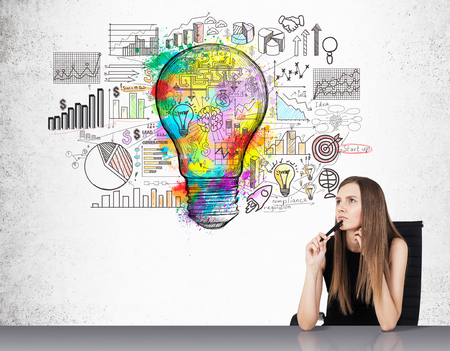 statistician: Portrait of businesswoman sitting near concrete wall with colorful light bulb sketch and diagrams. Concept of statistician work