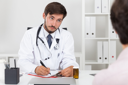 general practice: Doctor in white gown with beard looking at his patient in disbelieve. Concept of I dont buy it, mate Stock Photo