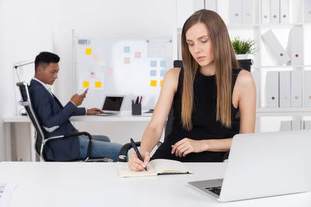 speculative: Pretty business lady is taking notes in her notebook. Her Asian colleague is looking at his phone screen. Concept of hard clerk work