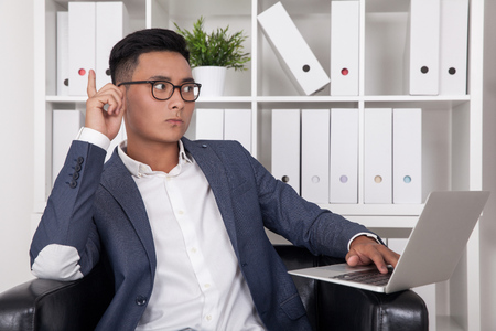 discovered: Serious Asian businessman in glasses telling his colleagues off camera what he has discovered about their competitors new marketing strategy