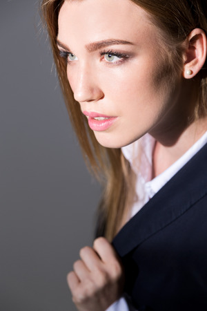 lapel: Gorgeous businesswoman looking to side standing against gray background and holding her lapel. Concept of pretty business lady Stock Photo